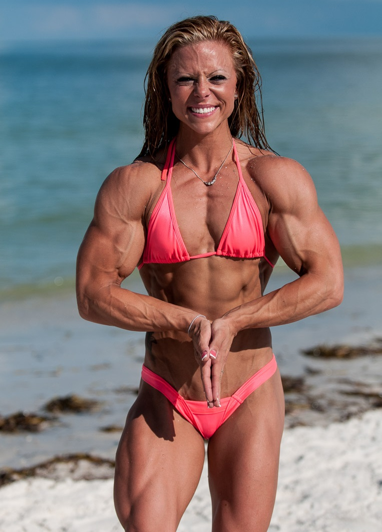 Dani Reardon standing on the beach in a pink bikini, flexing her ripped muscles for a photo