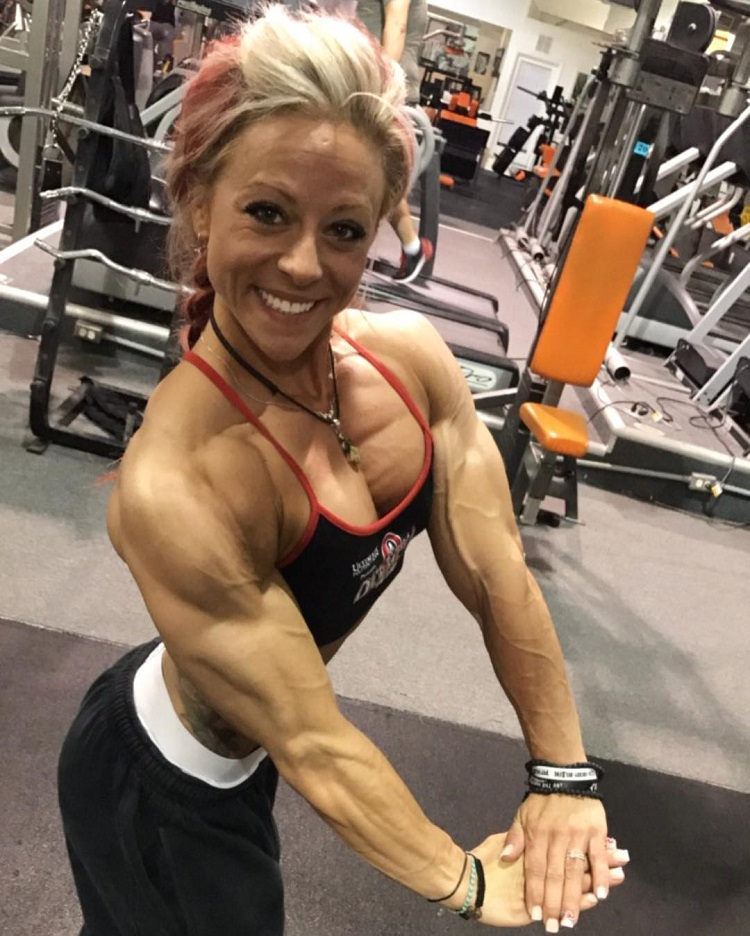Dani Reardon flexing her triceps for a photo looking fit and lean
