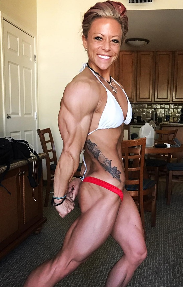 Dani Reardon flexing her triceps for a photo looking lean and aesthetic