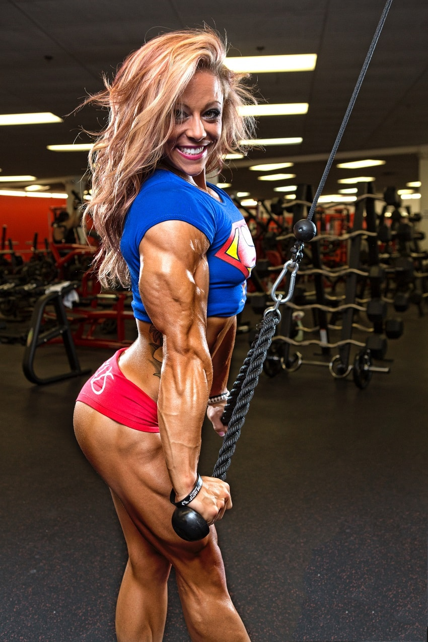 Dani Reardon doing cable triceps extensions looking ripped and muscular