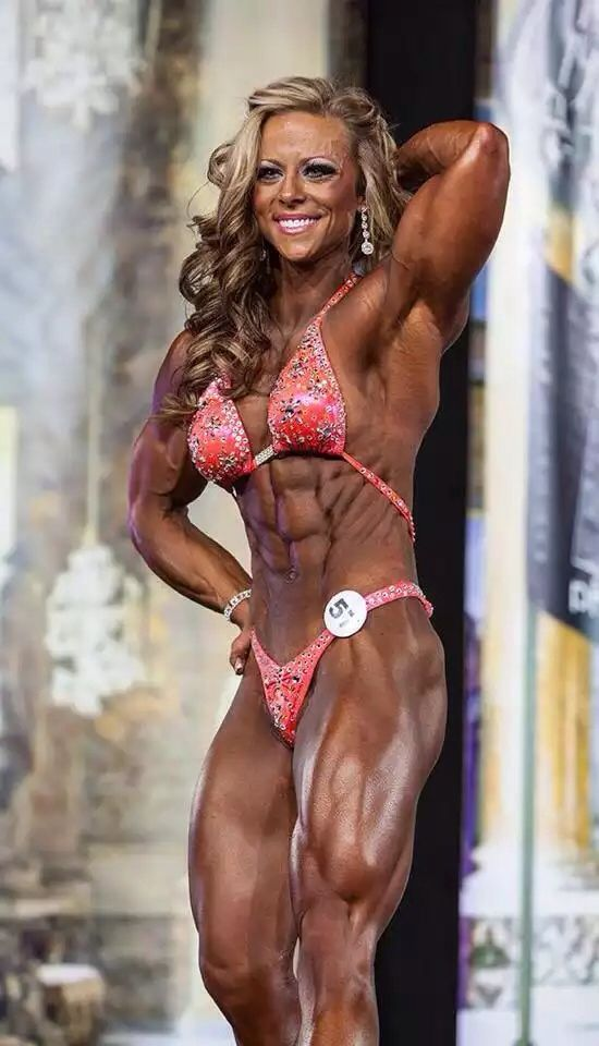 Dani Reardon posing on a bodybuilding stage looking ripped