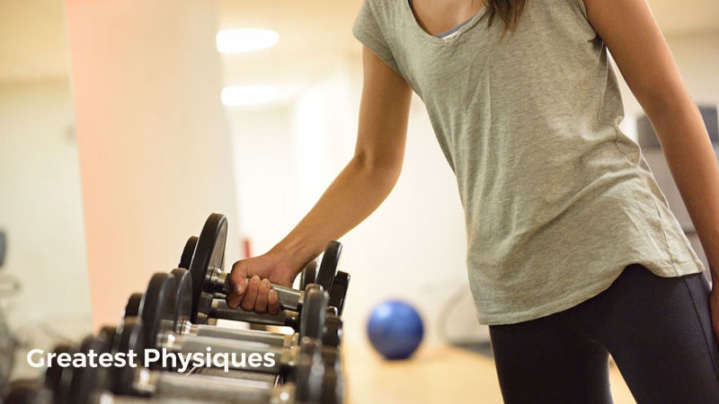 Woman in gym strength training lifting dumbbells from a rack