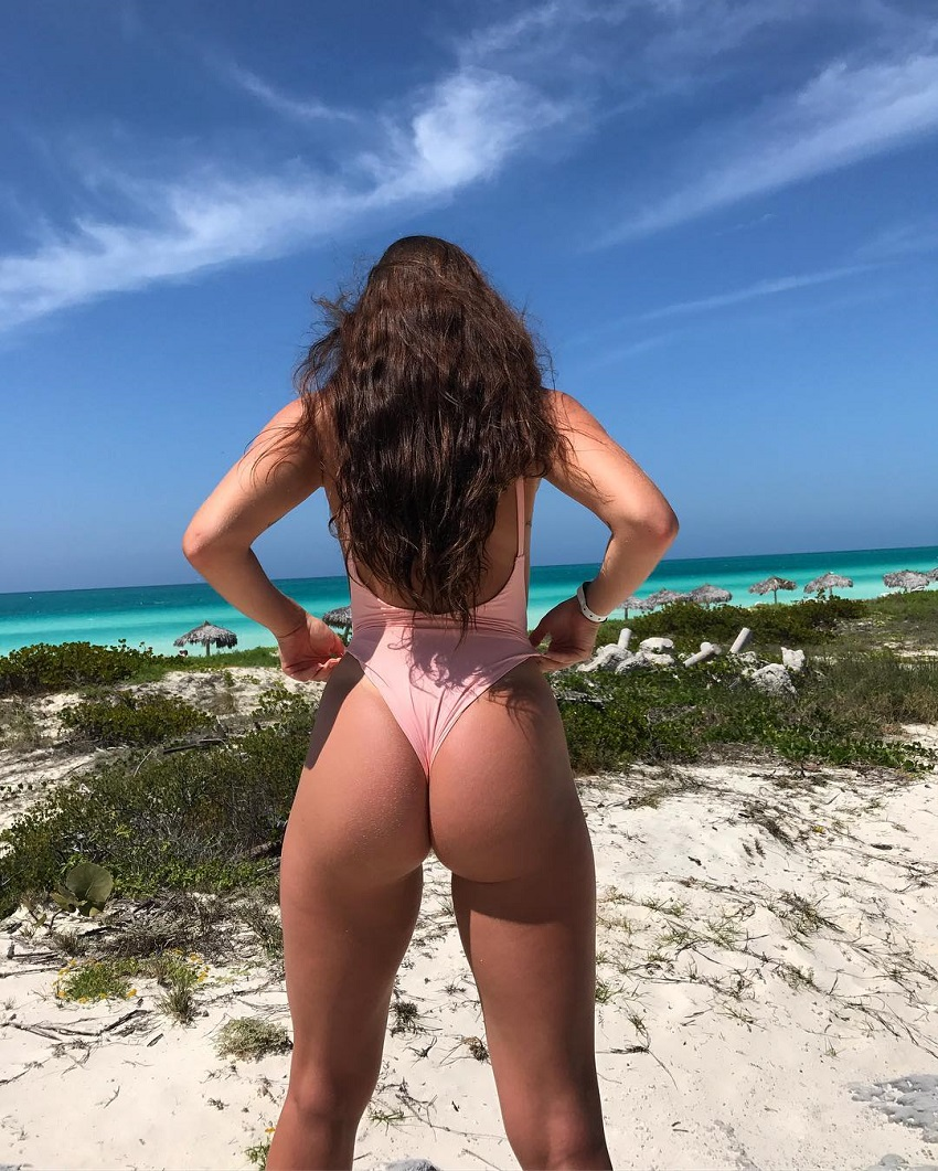 Gabby Scheyen standing on the sand near the beach showing off her amazing glutes
