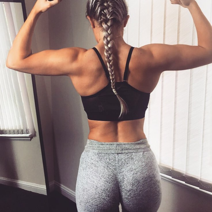 Jane Campbell flexing her arms from the back wearing grey yoga pants looking curvy and fit