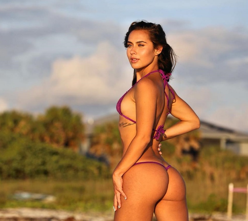 Janeece Sinclair posing outdoors during a sunset looking curvy and fit
