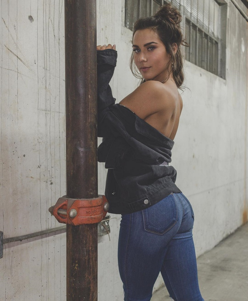 Janeece Sinclair posing in blue jeans and leather jacket showing off her curvy glutes