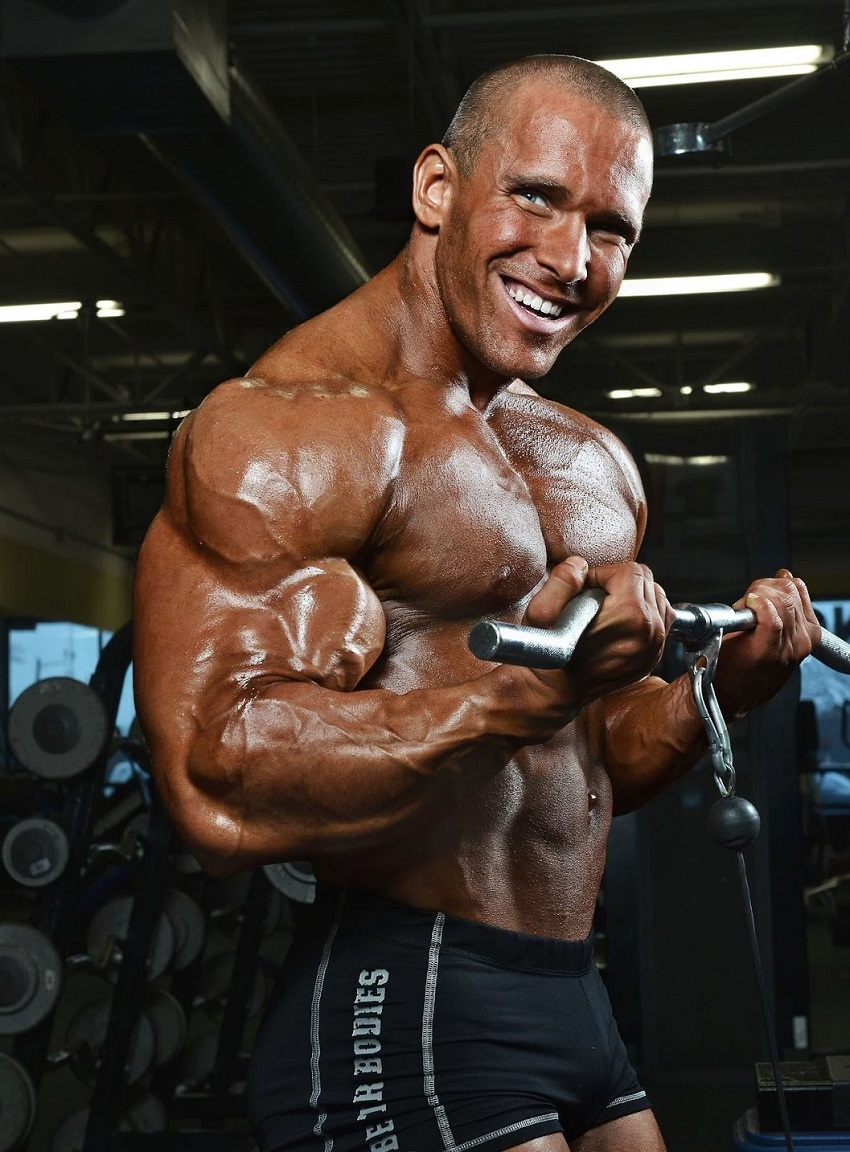 Jordan Janowitz doing cable biceps curls as a part of a photo shoot looking big and muscular