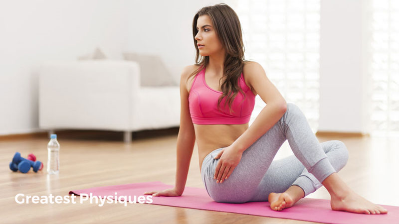Dark-haired, pretty female athlete in a pink sports top stretching on a yoga mat