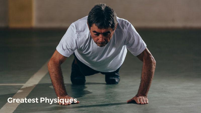 Older Hispanic man performing press-ups in the gym