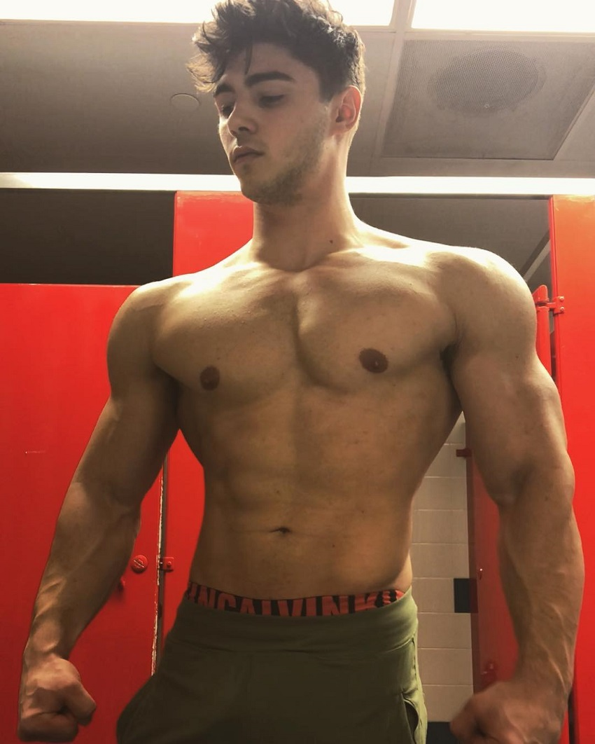 Qwin Vitale posing shirtless for a photo his arms and chest looking chiseled and abs ripped