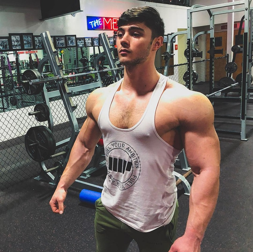 Qwin Vitale posing off in a white tank top in a gym looking healthy and fit