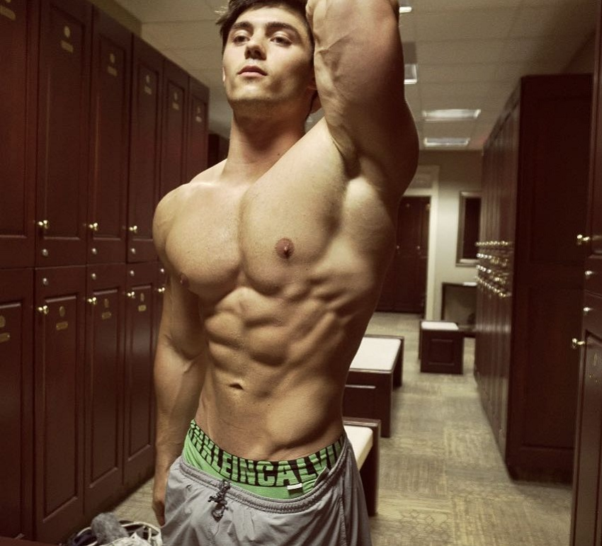 Qwin Vitale flexing his bulging abs and big chest for a photo, standing in a gym locker room