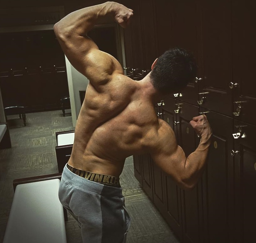 Qwin Vitale flexing his back and arms in a gym locker room