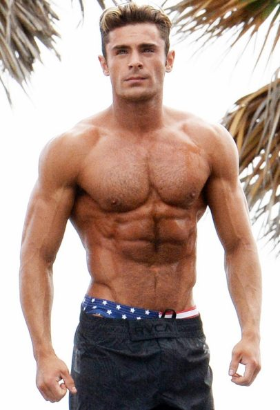 Zac Efron standing shirtless outdoors by the palm trees, looking ripped and muscular