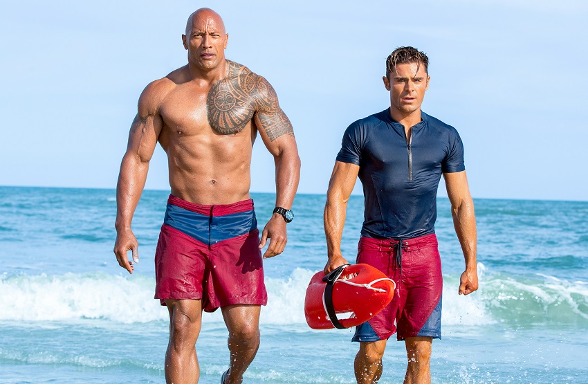 Zac Efron walking on the beach with The Rock Dwayne Johnson