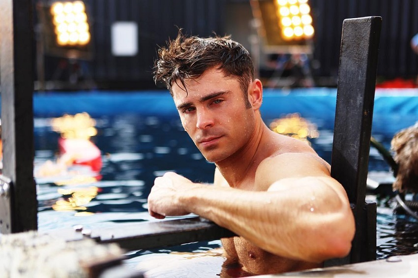 Zac Efron posing for a photo while standing in a pool