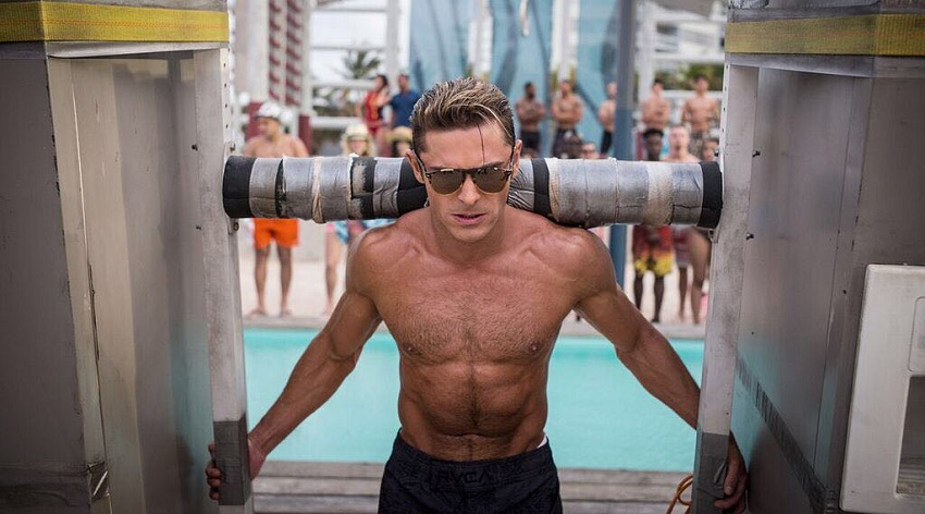 Zac Efron lifting a construct in front of numerous people that stand by the pool, looking ripped and fit