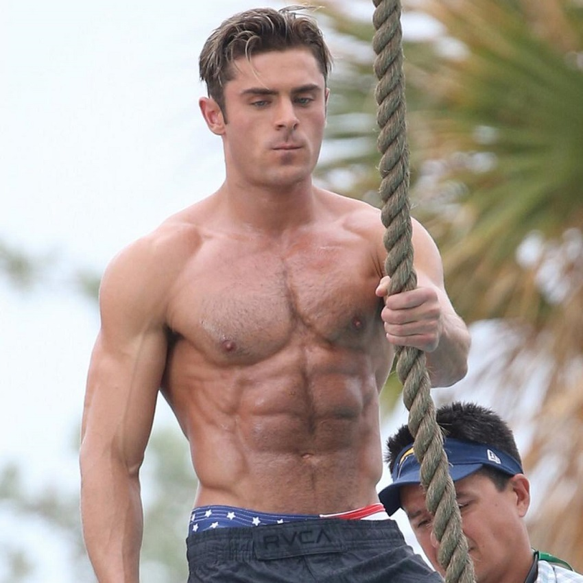 Zac Efron holding a rope while being shirtless, his physique looking chiseled and ripped