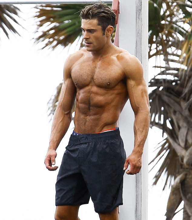 Zac Efron standing outdoors, showcasing his chiseled physique