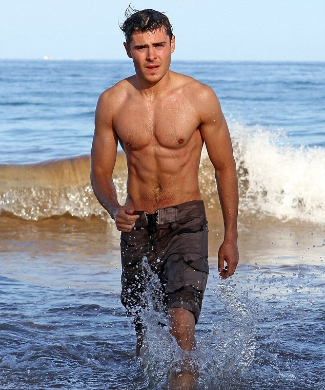 Zac Efron walking on the sea shore looking fit and lean