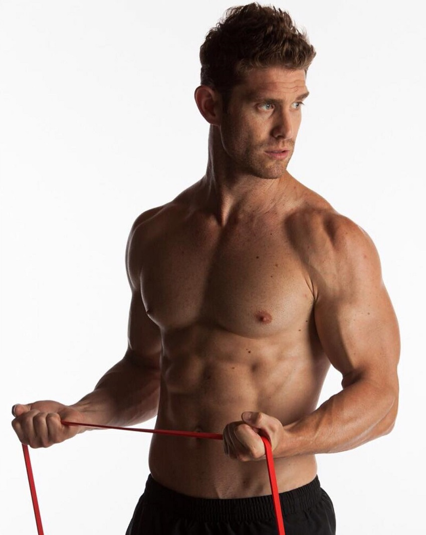 CJ Koegel posing shirtless with resistance bands in his arms, looking aesthetic and lean