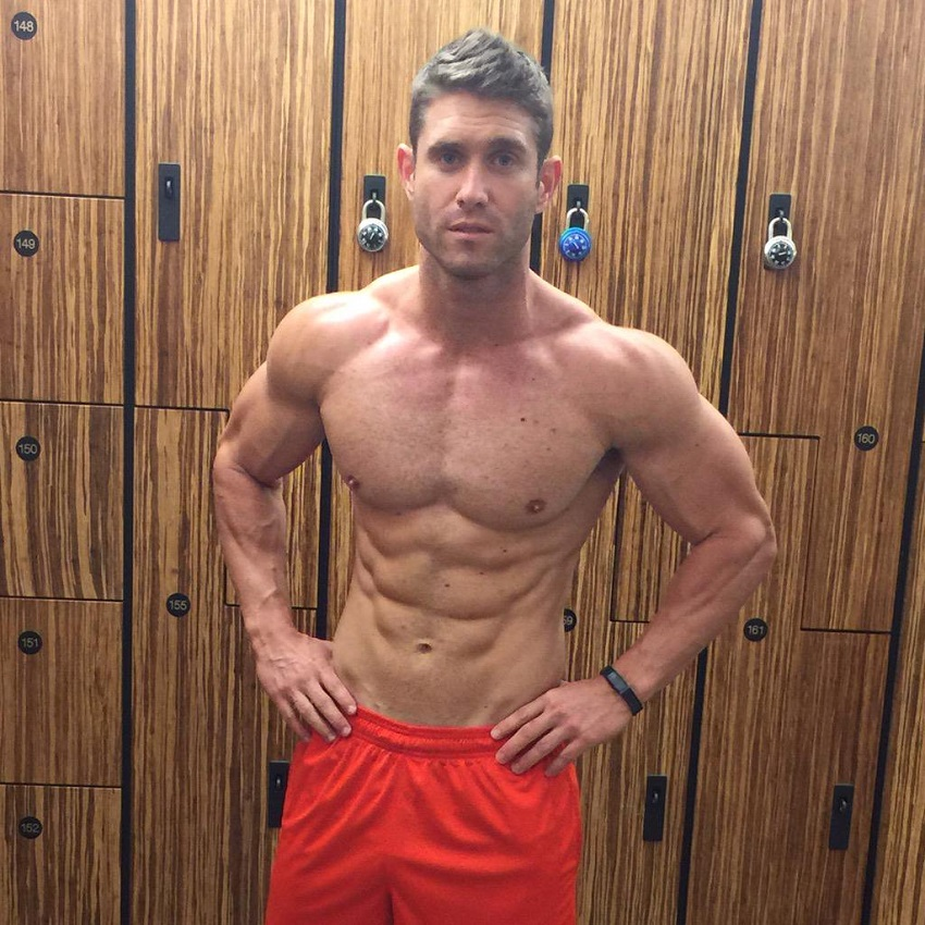CJ Koegel posing shirtless in a gym locker room looking ripped and lean