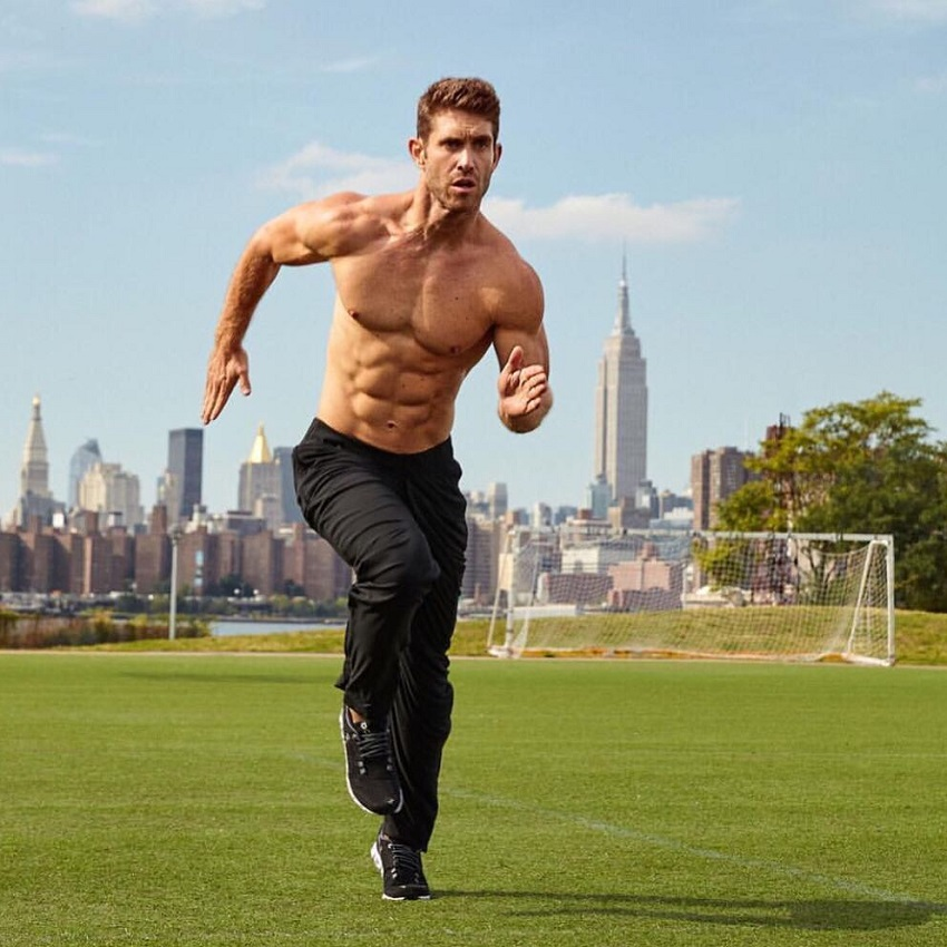 CJ Koegel running shirtless on a grass field looking big and ripped
