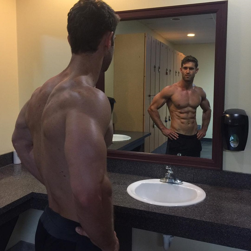 CJ Koegel looking at his big and ripped muscles in the mirror