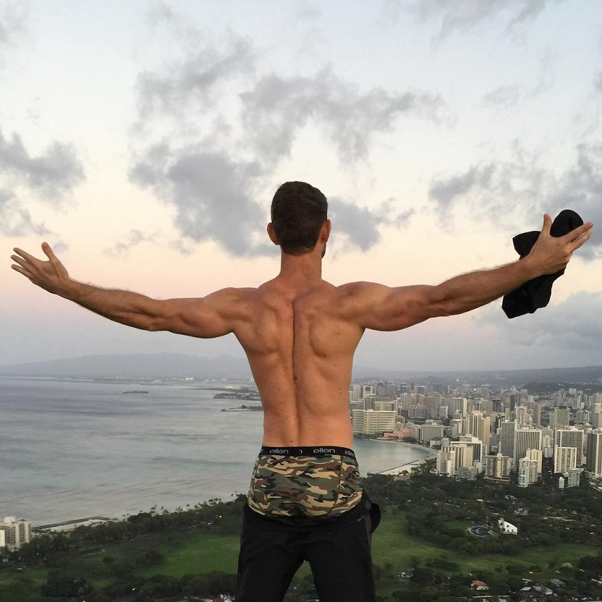 CJ Koegel overlooking a big city and nature with his arms wide open, looking muscular and lean