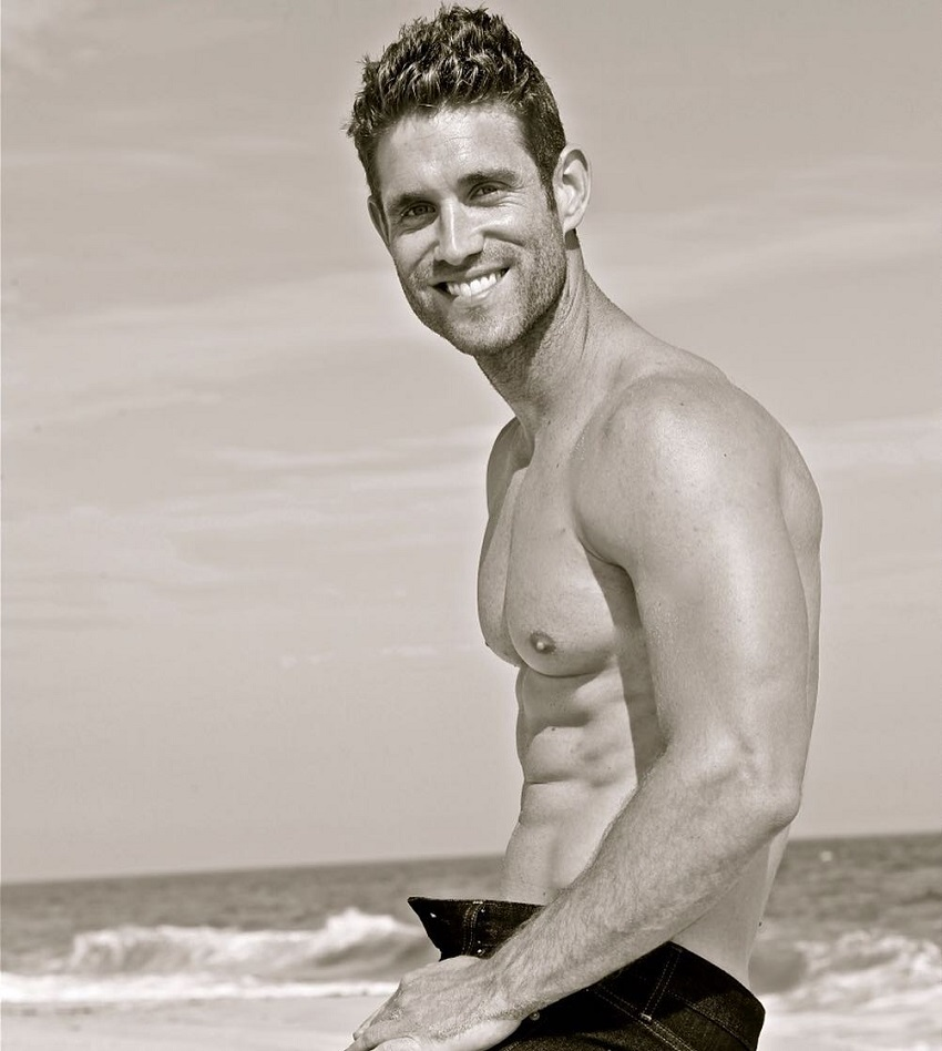 CJ Koegel sitting on a beach smiling for a photo looking lean