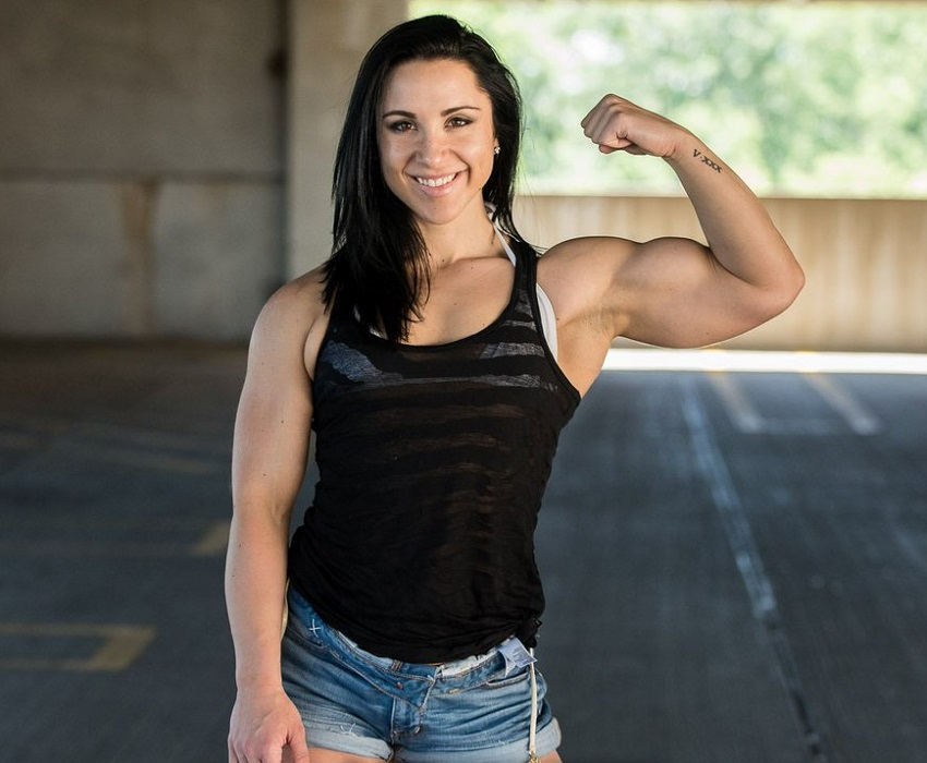 Chloe Sannito flexing her awesome biceps and smiling for a photo