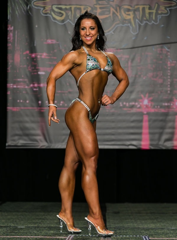 Chloe Sannito posing on a bodybuilding fitness stage