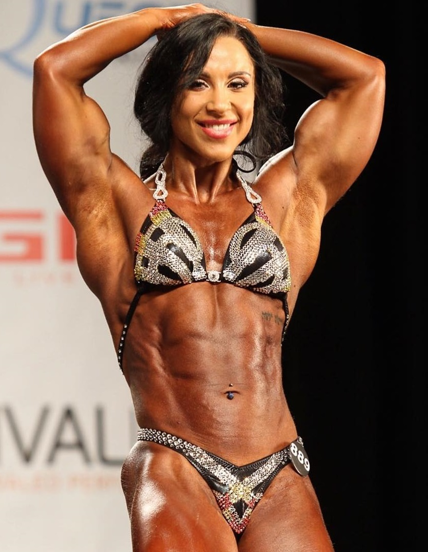 Chloe Sannito flexing her abs on a bodybuilding stage