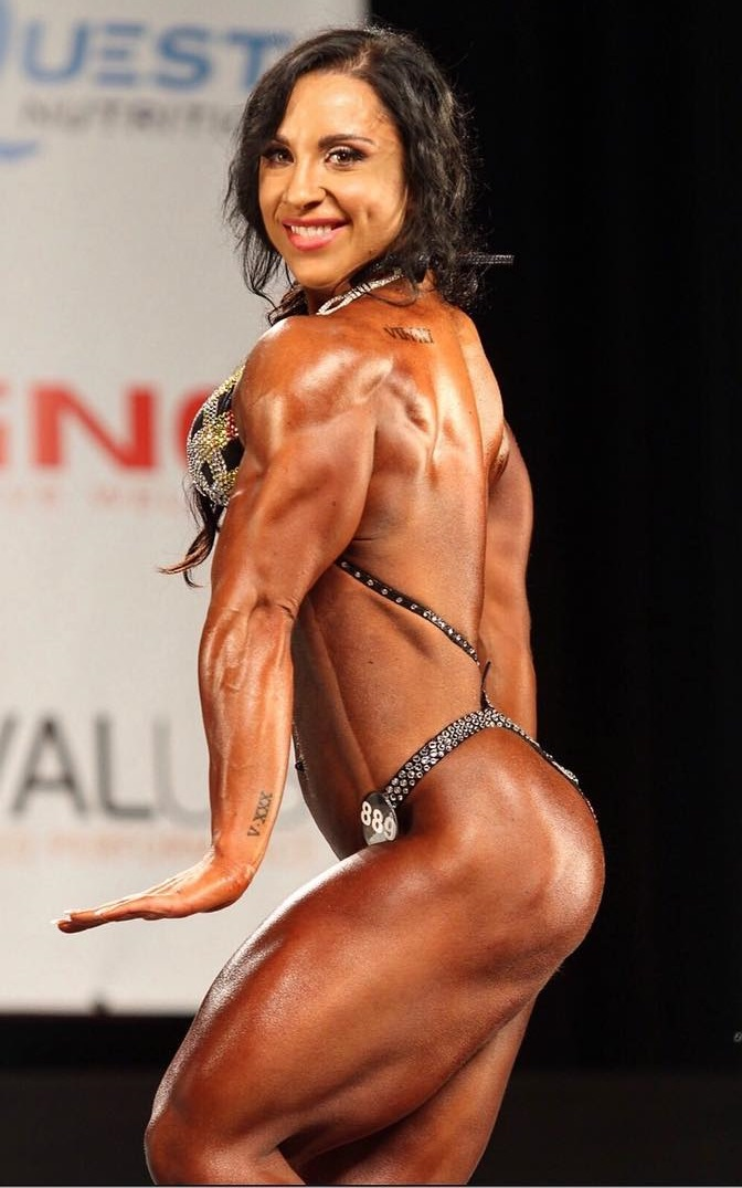 Chloe Sannito flexing her triceps and back on a bodybuilding stage