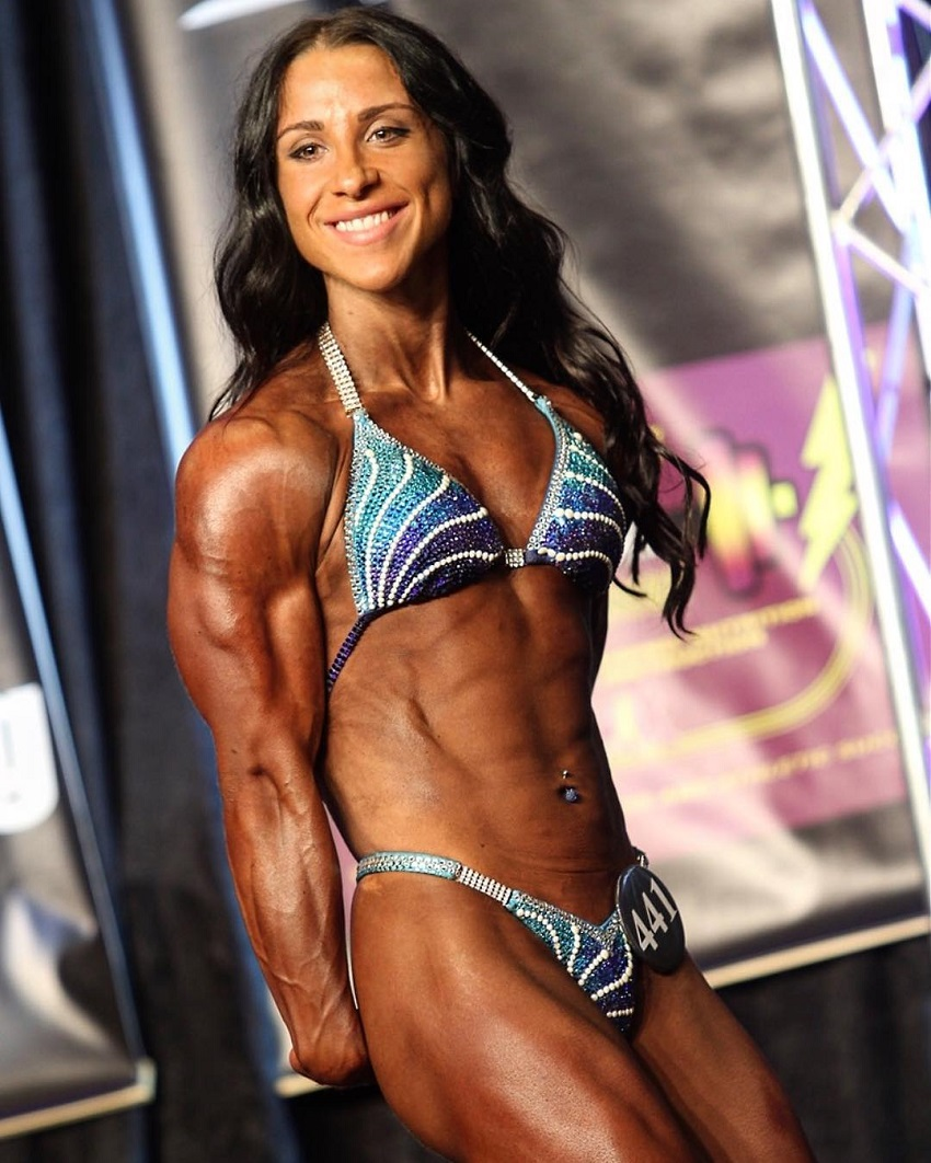 Chloe Sannito posing on a bodybuilding stage