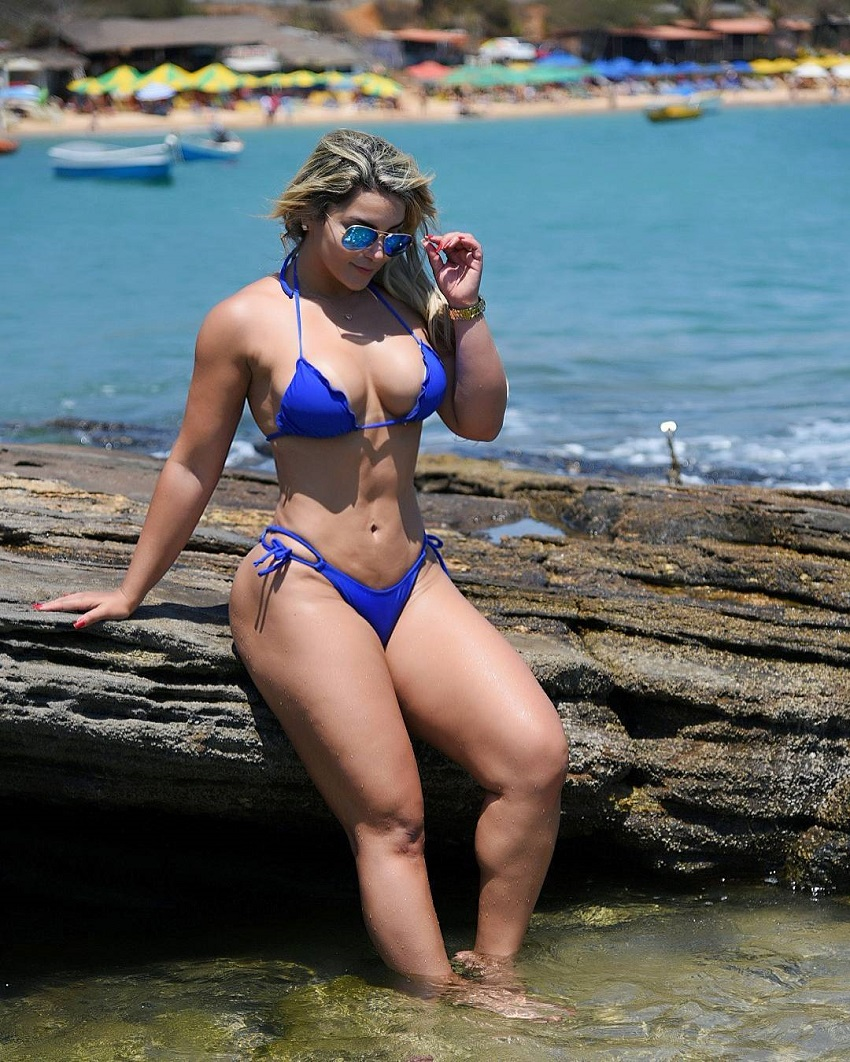 Daiane Lopes sitting on a log on a seashore looking fit and lean in her blue bikini