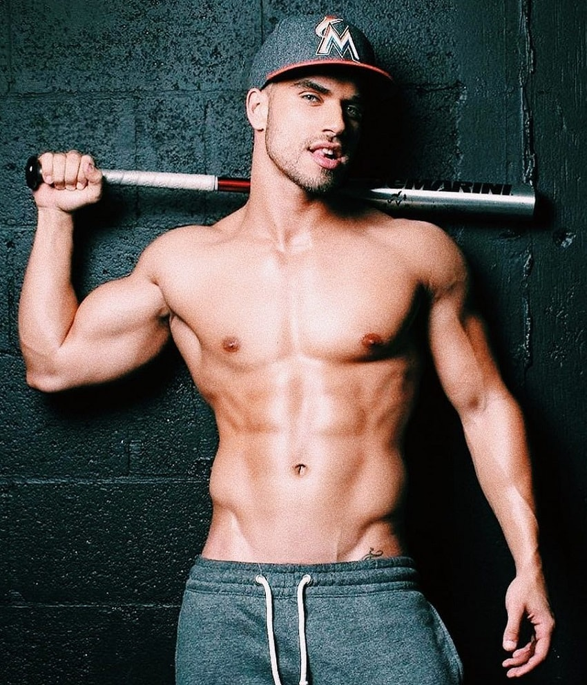 Darian Alvarez posing shirtless with a sledgehammer in his hand