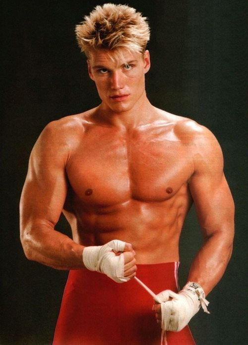 Dolph Lundgren posing for a photo wrapping his hands for a boxing match, looking strong and ripped