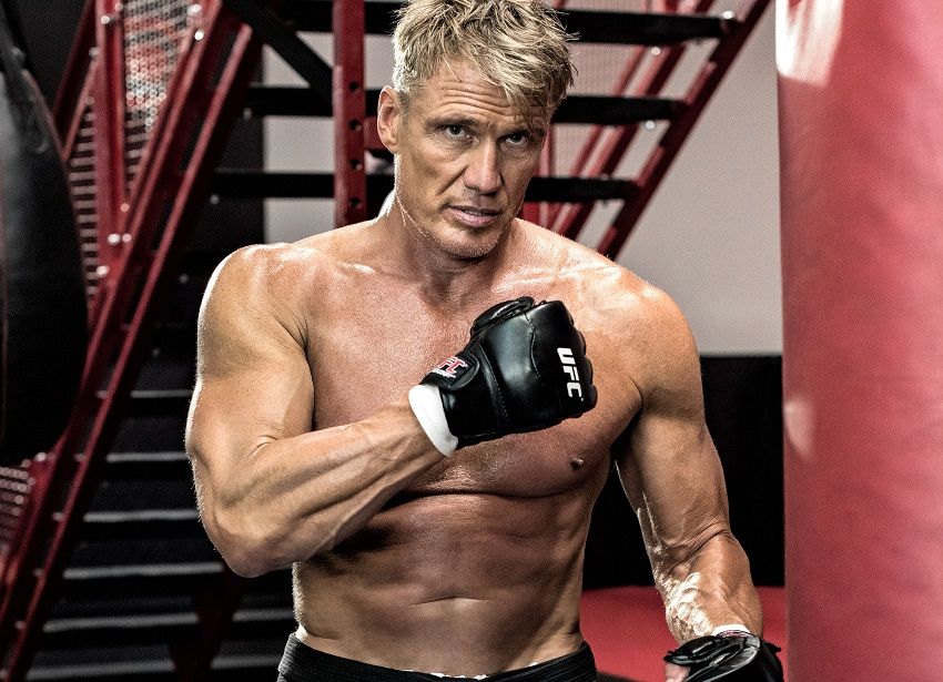 Dolph Lundgren posing shirtless and waring black boxing gloves looking ripped