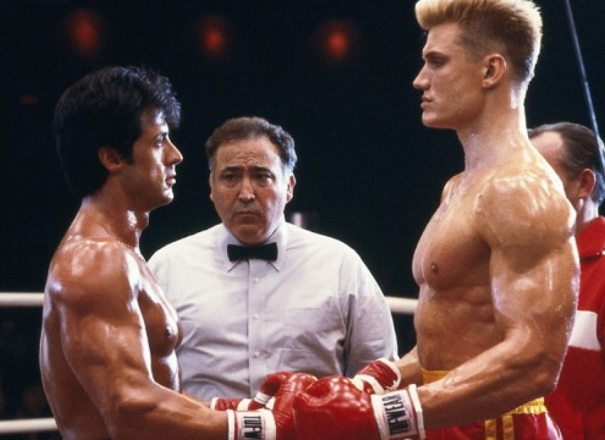 Dolph Lundgren standing in the boxing ring with Sylvester Stallone, looking into each others eyes before the beginning of the fight