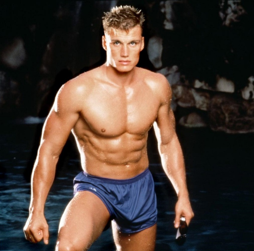 Dolph Lundger in his younger days, posing shirtless for a photo, looking ripped