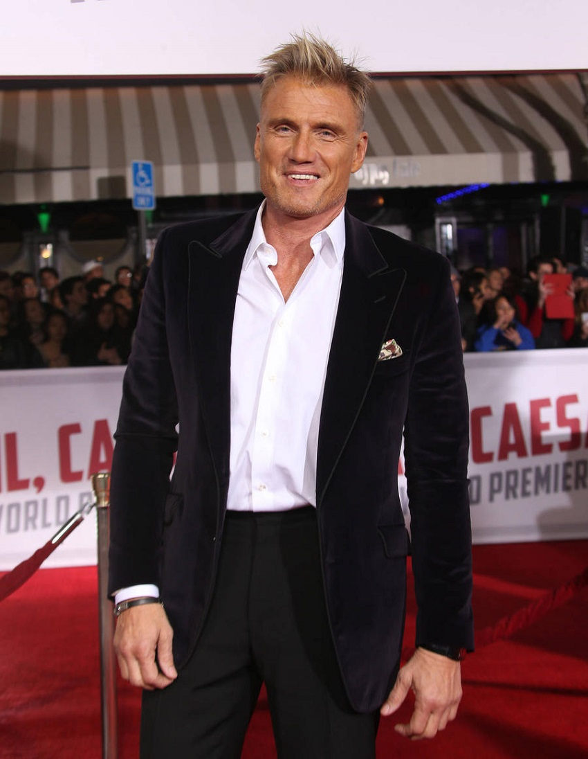 Dolph Lundgren walking down the red carpet in his black and white suit looking strong and healthy