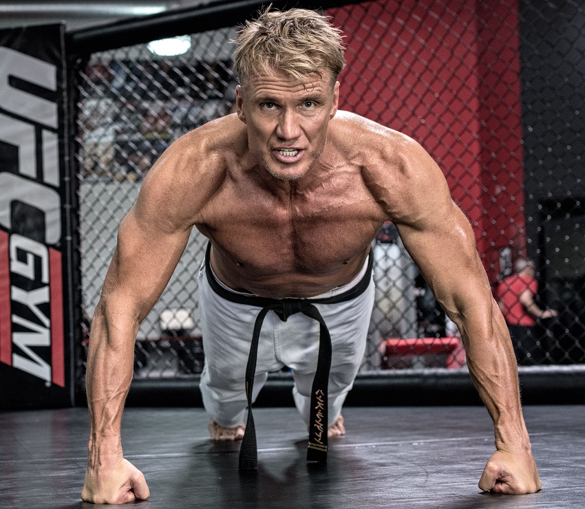 Dolph Lundgren doing shirtless pushups looking ripped