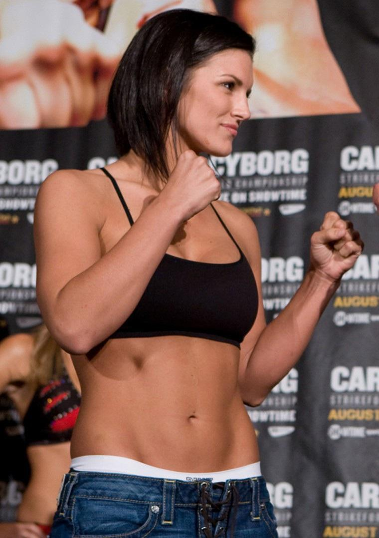 Gina Carano standing in a boxing stance looking at her opponent during a press-conference
