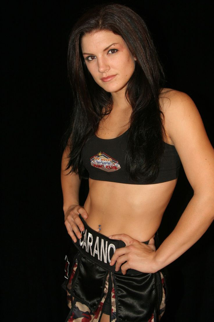 Gina Carano posing for a photo in her MMA outfit looking fit and strong