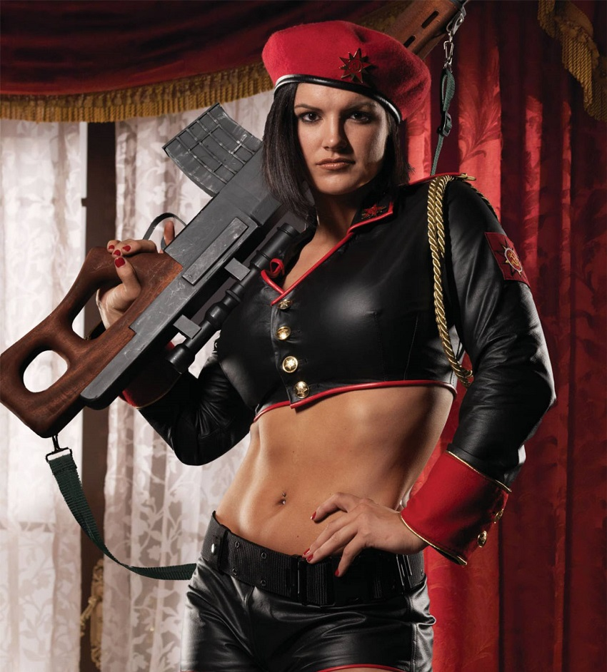 Gina Carano in one of her movie roles holding a rifle in her arms looking fit and lean