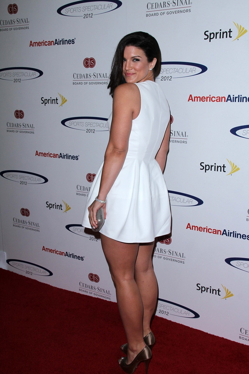 Gina Carano standing on a red carpet in a white dress looking fit and healthy