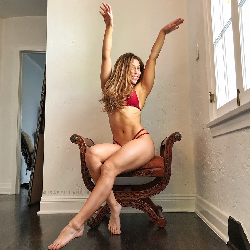 Isabel Lahela stretching while sitting in a chair wearing a bikini, looking fit and lean