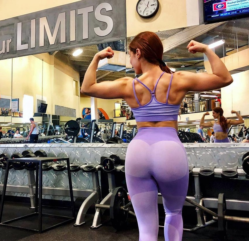 Isabel Lahela flexing her strong arms and back in the gym