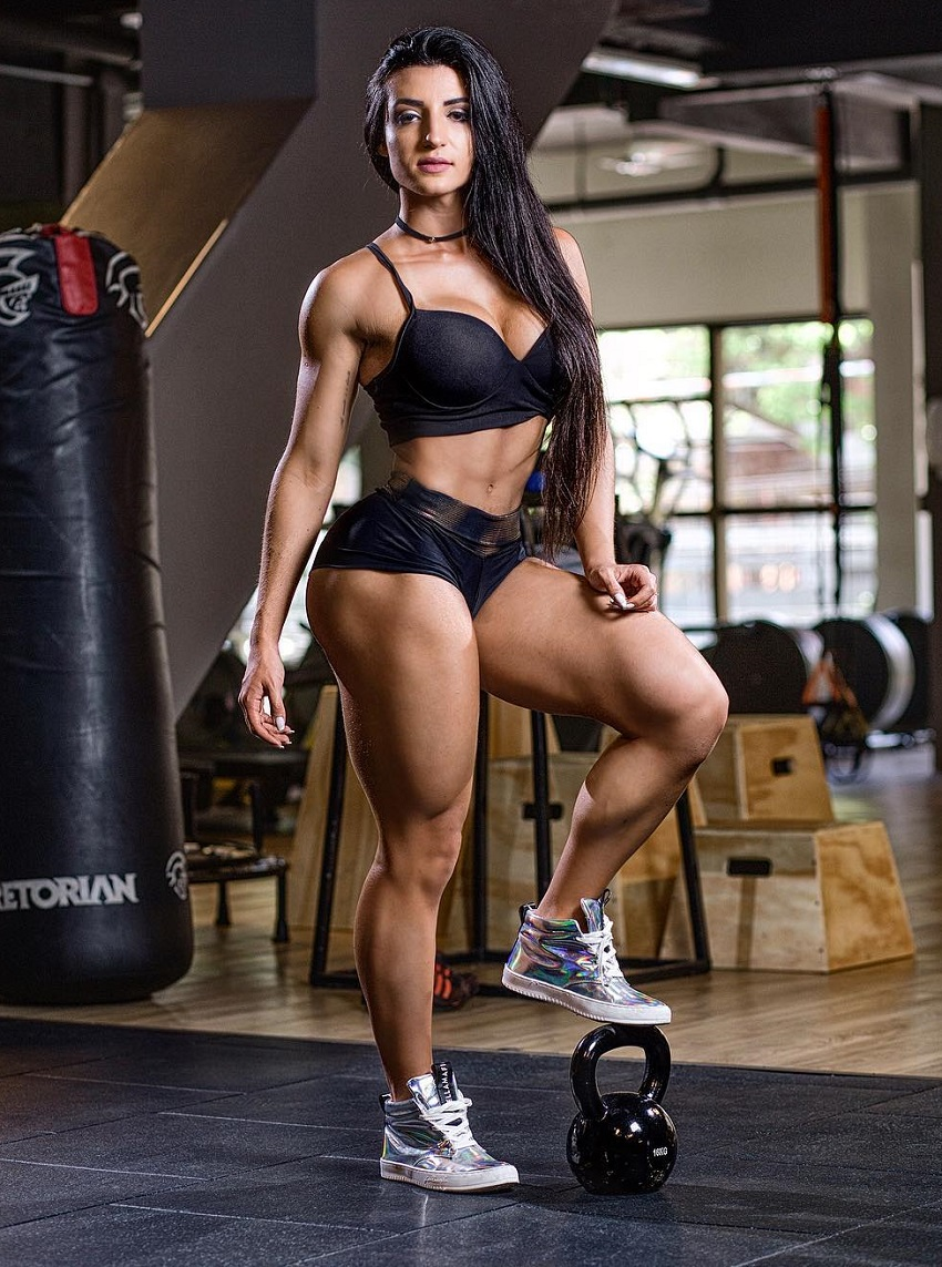 Jessica Basso Ortiz standing in a gym posing with a dumbbell beneath her foot looking fit and curvy